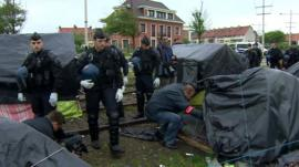 Police search tents at the camp in Calais