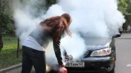 Woman sprays fire extinguisher at car