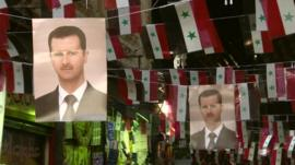 Pictures of Bashar al-Assad hanging amongst Syrian flags