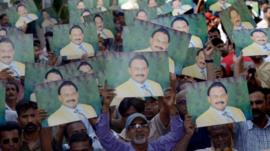 Supporters of Pakistan's MQM party hold photographs of their party leader Altaf Hussain