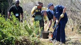 British Police officers dig for evidence during a search of an area of scrubland