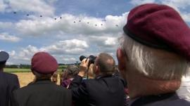 Veterans watch the parachute drop as part of the D-Day ceremony
