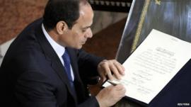 President Abdel Fattah al-Sisi signs a document of transferring authority