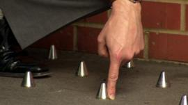 Hand pointing to metal studs outside block of flats