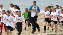 Anthony Ogogo runs with children on Lowestoft beach