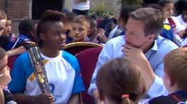 David Cameron talks to a young athlete who is holding the Queen's Baton.