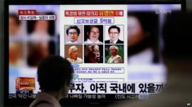 A woman watches a TV news programme showing the reward poster of Yoo Byung-eun
