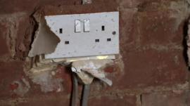 A plug socket in a bare wall