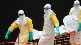 Medecins Sans Frontieres doctors carry the body of an Ebola victim