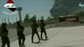 Off-air TV pictures of troops on ground at Baiji refinery, black smoke rising