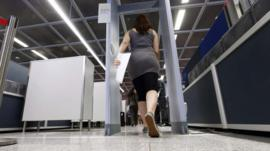 A woman goes through a security check at Frankfurt Airport