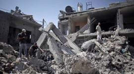 Palestinians search in the rubble of a destroyed house where eight members of the Al Haj family were killed in a strike early morning in Khan Younis refugee camp, southern Gaza Strip on Thursday, July 10, 2014