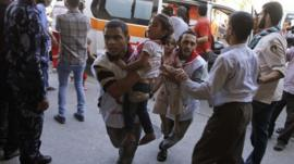 Palestinian medics run carrying children wounded in attack on UN shelter in Beit Hanoun