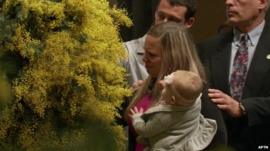 Woman mourner with baby being comforted as she takes part in MH17 memorial service in Melbourne's St Patrick's Cathedral