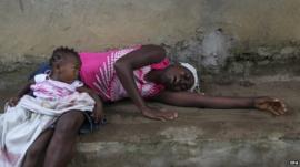 Liberian woman weeps over the death of a relative from Ebola on the outskirts of Monrovia