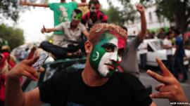 Pakistani supporters of cricketer-turned-politician Imran Khan, pose with their faces painted in party colours