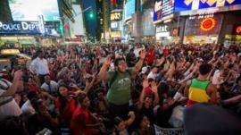 Protesters raise their arms in in New York's Times Square in a show of solidarity for shot US teenager Michael Brown
