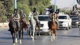 Militant Islamist fighters ride horses as they take part in a military parade along the streets of Raqqa, northern Syria, 30 June 2014