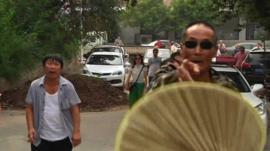 Policeman pointing at camera, fan partially blocking lens