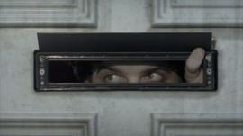 A man looking out of his letterbox