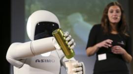 Honda's Asimo humanoid robot pours a drink into a cup