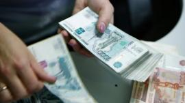 An employee of a bank counts rouble banknotes in Moscow