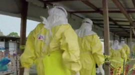 Healthcare workers in biohazard suits
