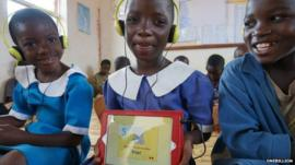 Malawian child holds up app