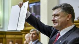 Ukrainian President Petro Poroshenko shows the Ukraine-EU Association Agreement