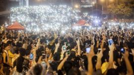 Pro-democracy protesters hold up their mobile phones as lights in front of the Hong Kong government offices on day three of the mass civil disobedience campaign Occupy Central in Hong Kong