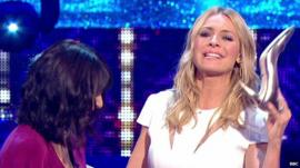 Claudia Winkleman (left) looks on as Tess Daly (right) holds up her silver shoe