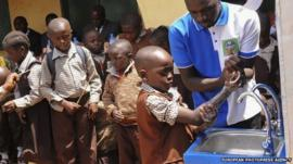 Nigerian pupils of Powa International Childrens School wash their hands as part of the 2014 Hand Washing Day Ebola sensitization campaign in Abuja, Nigeria