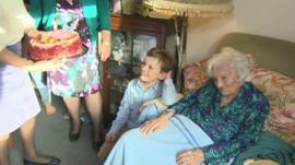 Gladys Hooper receiving her birthday cake, with a great-grandchild by her side