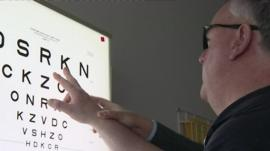 Man with macular degeneration looks at board with letters