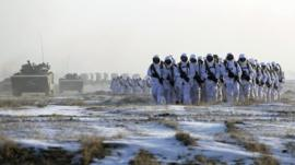 Soldiers and vehicles of the People's Liberation Army (PLA) Marine Corps march on a snow-covered field during a military drill in Jilin province, file pic from January 2015