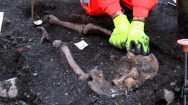 Archaeologist pulling up bones