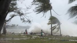 In this image provided by UNICEF Pacific people walk along the shore where debris is scattered in Port Vila, Vanuatu, Saturday, March 14, 2015