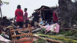 Local residents look through the remains of a small shelter in Port Vila, the capital city of the Pacific island nation of Vanuatu March 14, 2015