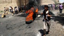 Yemeni protesters shout slogans and set alight tires during clashes following a protest against the Houthi takeover of several state facilities in the central city of Taiz, Yemen, 23 March 2015.