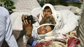 People prepare to sleep outside on a street in Kathmandu