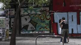 Youths hug outside closed shop in Athens