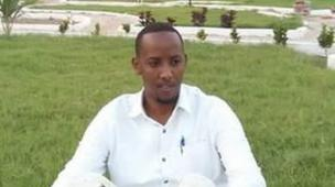 Journalist Abdinur Mohamed Ahmed sits on the grass at Peace Garden in Mogadishu.