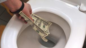 'Putting money down a toilet' from the web at 'http://ichef-1.bbci.co.uk/news/304/cpsprodpb/14F04/production/_88446758_toilet.jpg'
