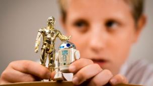 'A boy playing with two Star Wars figures' from the web at 'http://ichef-1.bbci.co.uk/news/304/cpsprodpb/1546/production/_86664450_edit-boy.jpg'