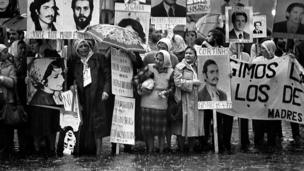 Madres con pañuelos blancos en la cabeza llevan carteles con las fotos de hombres y mujeres y mensajes que exigen el hallazgo de su paradero.