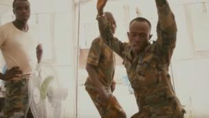 'Sierra Leonean policeman twerking' from the web at 'http://ichef-1.bbci.co.uk/news/304/cpsprodpb/1860D/production/_86735899_ebolatwerking.png'