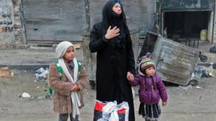 A Syrian woman arrives in Aleppo's Fardos with her children in Aleppo's Fardos neighbourhood after regime troops retook the area from rebel fighters, 13 December 2016