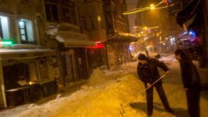 ترکی کے دارالحکومت استنبول میں ایک سٹور کا مالک برف ہٹا رہا ہے۔