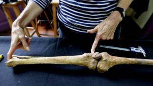 Mulher mostra um osso