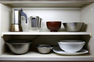 Bowls sit in a kitchen cupboard in the apartment of minimalist Fumio Sasaki